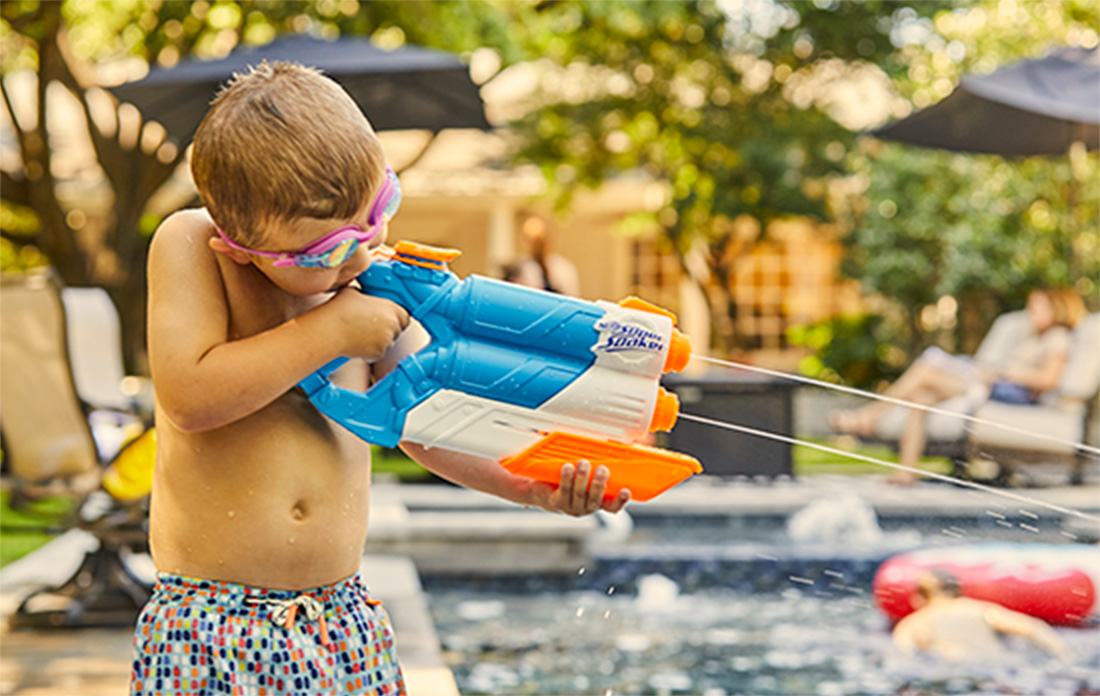 happy boy playing poolside with water pistol and swim goggles.