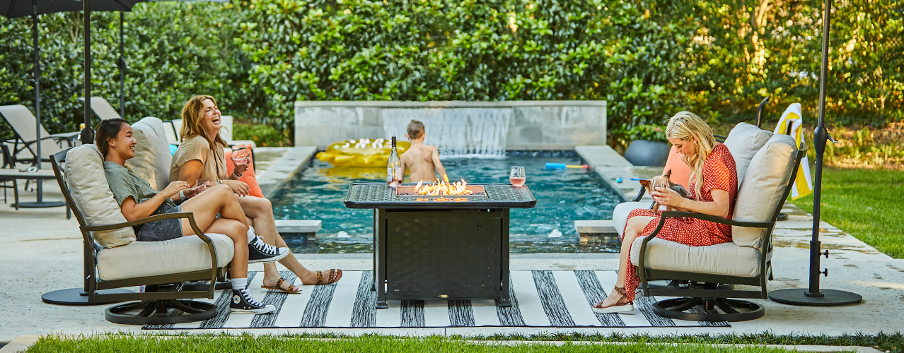 Mallin lounge chairs and fire table by a pool